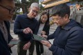 Apple CEO Tim Cook (centre, left) is shown how to write calligraphy on an iPad in this file photo taken in Beijing, Oct. 10, 2018. Apple lost its No 1 position in China's tablet market in the first quarter. Photo: Xinhua