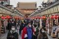 Tourists wearing masks stroll through Tokyo's Asakusa district, in March. Photo: EPA-EFE