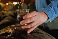 A worker at Bruichladdich distillery takes a whisky sample from a cask. Photo: Getty Images