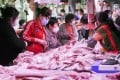 Consumers are seen buying pork at a market in Beijing on May 5. Prices have eased since the Lunar New Year amid rising supply from local and import sources. Photo: Kyodo