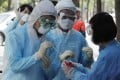 Medical staff wearing protective suits gather samples from people during Covid-19 testing at a hospital in Seoul, South Korea. Photo: AP