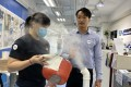 Salom Yiu Kam-shing demonstrates how his disinfection product sterilises a mask with fencer Alison Yu Chui-yee. Photo: Chan Kin-wa