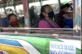Philippine passengers wear masks as they ride a mini bus, known as a jeepney. Photo: EPA
