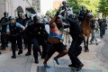 Riot police chase a man as they rush protestors to clear the area across from the White House. Photo: Reuters