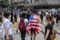 A demonstrator in Hong Kong is draped in an American flag during a protest against a planned national security law, in the city's Wan Chai district on May 24. Photo: Bloomberg
