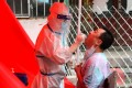 A medical worker takes a sample from a resident in Mudanjiang as the city begins mass screening for the coronavirus. Photo: AFP