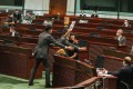 Legislative Council security guards tackle Raymond Chan after he left his seat during the debate on the national anthem law. Photo: Nora Tam