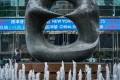 The stock ticker is seen behind a sculpture at Exchange Square in Hong Kong. Photo: Bloomberg