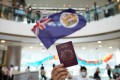 A Hong Kong protester holds up a BN(O) passport while another waves the British colonial flag, during a demonstration at a mall in the city's Central business district on May 29. Photo: Winson Wong