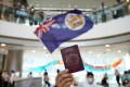 A protester holds a BN(O) passport during a lunch hour demonstration at the IFC shopping mall in Central. Photo: SCMP