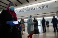 Passengers wearing protective face masks walk through the international arrivals hall of London's Heathrow Airport in London on June 8, when the UK began to impose a 14-day quarantine rule on most travellers. Photo: Bloomberg
