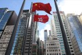 The Hong Kong and Chinese flags are seen against a backdrop of office buildings in the financial district of Central on June 11. Photo: Dickson Lee
