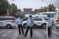 Police stand guard outside an entrance to the Xinfadi wholesale market district in Beijing on Saturday. Photo: AP