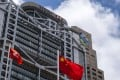 The Chinese and Hong Kong flags fly near the HSBC (left) and Standard Chartered buildings. Participating banks in Hong Kong will start accepting registrations for the government's HK$10,000 cash payout scheme on June 21. Photo: Bloomberg