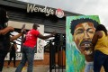 People use their cellphones on Sunday to document a muralist painting the face of Rayshard Jones outside a burned Wendy's in Atlanta following his shooting death in the restaurant parking. Photo: AFP