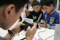 Chinese kids play mobile games on smartphones during an expo in Chengdu city, Sichuan province, on 20 October 2011. Photo: Imaginechina