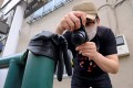 Japanese photographer Koji Ishii takes pictures of a lost glove in Tokyo. Photo: AFP