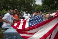 People fold an American flag near an empty casket during a Juneteenth celebration in Tulsa, Oklahoma. Photo: Bloomberg