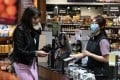A cashier wears a face mask while serving a customer in Sydney on June 17, 2020. Photo: Reuters
