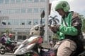 A Go-Jek motorcycle driver checks his smartphone, while preparing for another delivery in Jakarta, Indonesia. Gojek managers pledged to funnel 25 per cent of their salaries over the next year into a fund designed to support drivers, merchants and partners, following the company's decision to cut 430 jobs. Photo: Bloomberg