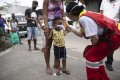 A member of the Red Cross checks the temperature of a child at Rio de Janeiro's main wholesale market. Photo: AP