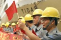 Workers wave Chinese flags during China Vice-Premier Li Keqiang's visit to the Suramadu bridge in Surabaya, East Java, on December 21, 2008. File photo: AFP