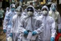 Indian health workers wearing personal protective equipment arrive at a coronavirus hotspot in Mumbai. Photo: EPA