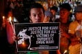 Protesters and residents hold lighted candles and placards at the wake of Kian delos Santos, a 17-year-old high school student who was among the minors killed by authorities. Photo: Reuters