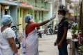 A health worker checks the temperature of a resident outside a containment zone in Hyderabad, India, on Tuesday. India's economy is set to contract by 4.5 per cent this year due the Covid-19 pandemic. Photo: AFP