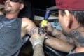 Tattoo artist Alexander Lawrence (right) covers a tattoo that contained the image of a swastika on the arm of Dylan Graves in Bellows Falls in the US state of Vermont. Photo: AP