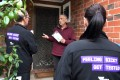 Health workers speak to a resident of the Melbourne suburb of Brunswick West as they encourage people to take coronavirus tests. Photo: AFP