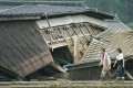 Residents walk beside a collapsed house in the flood-ravaged village of Kuma in Kumamoto prefecture, southwestern Japan. Photo: Kyodo