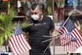Marvin Turcios puts out American flags at Ocean's 10 restaurant on Miami Beach. Photo: AP Photo