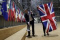 Staff remove the British flag from the European Council in Brussels on January 31 when Britain officially exited the EU, beginning an 11-month transition period. Photo: EPA-EFE