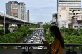 A pedestiran walks through Bangkok during peak hour. Photo: AFP
