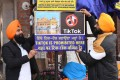 In this file photo taken on February 10, 2020 Sikh volunteers hang a sign reading 'Tiktok is prohibited here', at the Golden Temple in Amritsar. Photo: AFP