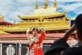 The US says it will impose visa restrictions on Chinese officials who block outsiders from visiting the Tibetan Autonomous Region and other Tibetan areas. Pictured, a visitor posing in front of the Jokhang Temple in Lhasa, capital of the autonomous region, on July 2. Photo: Xinhua