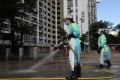Workers in protective gear disinfect the streets on July 5 in and around Long Ping Estate in Yuen Long, where a 59-year-old man living in one of the flats contracted coronavirus. It was the first locally-transmitted case of Covid-19 since mid-June. Photo: Dickson Lee