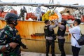 Police remove the body of an Indonesian crew member on a Chinese fishing boat after he was killed in Batam. Photo: AFP