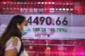 Hong Kong's benchmark, the Hang Seng Index, stampeded into a bull market last week. Here, a woman walks past a bank's electronic board showing the index level at Hong Kong stock exchange on June 30, 2020. Photo: Associated Press