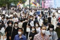 People wearing face masks walk in Tokyo's Shibuya area. The number of coronavirus cases globally closed in on 13 million on Monday. Photo: Kyodo