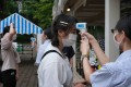 Visitors to a Tokyo amusement park have their temperatures checked. Photo: AFP