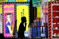 A man wearing a face mask walks past signboards for bars in Tokyo's Shinjuku district. Photo: Reuters