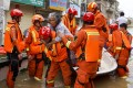 Firefighters bring a villager to safety during their rescue mission on Saturday. Photo: Tom Wang