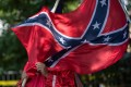 A member of the Ku Klux Klan holds a Confederate flag over his face during a rally. Photo: AFP