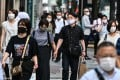 People wearing face masks walk in a street in Tokyo on July 20, as Japan's death toll eclipsed 1,000, and 168 new cases were recorded in the capital. Photo: AFP