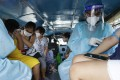 Health workers collect blood samples inside a jeepney bus at a free Covid-19 drive-through testing facility in Manila. Photo: AP