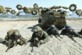 Marines of the US, left, and South Korea, wearing blue headbands, take positions after landing on a beach during a joint military combined amphibious exercise in 2016. Photo: Yonhap via AP