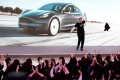 Tesla's chief executive officer Elon Musk throwing off his coat for a jig onstage during a delivery of Tesla's China-made Model 3 cars in Shanghai on January 7, 2020. Photo: REUTERS