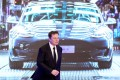 Tesla's CEO Elon Musk walks in front of an image of Tesla's Model 3 car in Shanghai on January 7. Photo: Reuters